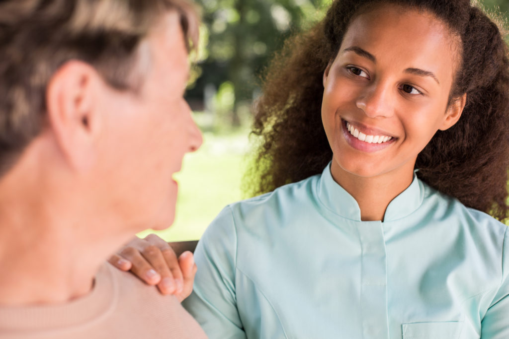 Senior woman talking with African American nurse